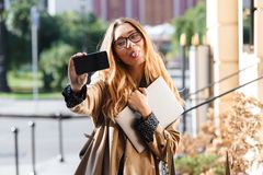 Photo of happy woman 20s holding laptop and using smartphone in city street. Photo of happy woman 20s holding laptop and using smartphone while walking through stock photos