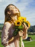 Beautiful young woman holding sunflowers stock photo