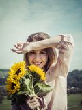 Happy young woman holding sunflowers. Photo of a happy young woman holding sunflowers in the sunshine stock images