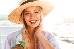 Photo of happy young woman 20s in summer straw hat laughing, and. Photo of happy young woman 20s in summer straw hat laughing and drinking cocktail during Royalty Free Stock Photography