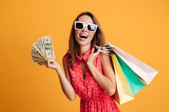 Photo of happy young woman in sunglasses holding fan of money an Stock Image