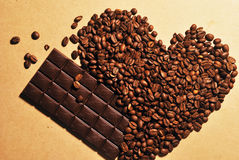 Photo of heart shaped coffee beans and chocolate bar on yellow background Royalty Free Stock Photography