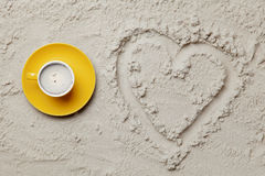 Photo of heart shaped drawing and cup of coffee on the sand. On the beach stock photo