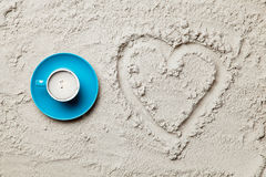 Photo of heart shaped drawing and cup of coffee on the sand. On the beach stock images
