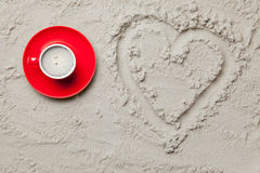 Photo of heart shaped drawing and cup of coffee on the sand. On the beach stock image