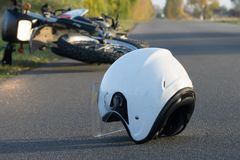 Photo of helmet and motorcycle on the road, the concept of road. Photo of helmet and motorcycle on road, the concept of road accidents Royalty Free Stock Image