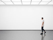 Photo of hipster in modern gallery looking at the empty canvas. Blank mockup, motion blur Royalty Free Stock Image
