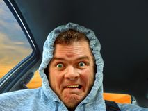 Hoodie frightened driver. Photo of a hoodie driver with frightened looking expression on face Stock Image
