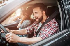 Photo horizontale du type émotif et sûr conduisant la voiture Il semble simple et criard La fille est Image stock