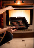 Photo of housewife putting pan with cookies in oven Stock Photos