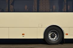 Photo of the hull of a large and long yellow bus with free space for advertising. Close-up side view of a passenger vehicle for t Royalty Free Stock Image