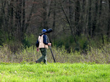 Photo hunter. Photographer hiking into the woods looking for images with a big zoom on his camera Stock Photo