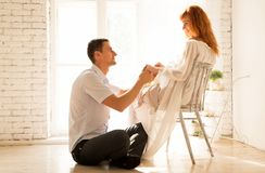 Husband sitting on the floor, pregnant woman on a chair. The husband looks affectionately at his wife. Photo of husband sitting on the floor, pregnant women on a Stock Image
