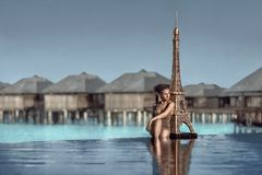 Beautiful female portrait with the Eifel tower on a beach. Royalty Free Stock Photo
