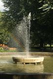 Fountain with a rainbow at the forest royalty free stock image