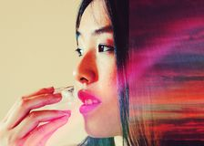 Photo illustration of model applying ice cube to lips with warm rays of sunset reflected in her hair. Photo illustration of a young Asian model placing a cold stock photo