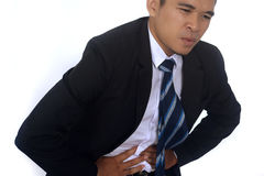 Photo image of a handsome asian businessman suffering from abdominal pain. Isolated on white Royalty Free Stock Image