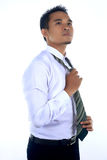 Photo image of a handsome attractive young Asian businessman dre. Ssing, fixing his tie and ready to work in formal wear Stock Photo