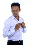 Photo image of a handsome attractive young Asian businessman dressing, button up his shirt. Ready to work in formal wear Stock Images