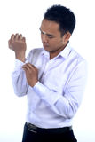 Photo image of a handsome attractive young Asian businessman dressing, button up his shirt sleeve. Ready to work in formal wear Stock Images