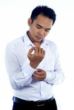 Photo image of a handsome attractive young Asian businessman dressing, button up his shirt sleeve. Ready to work in formal wear Royalty Free Stock Image