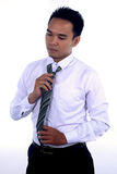 Photo image of a handsome attractive young Asian businessman dressing, fixing his tie and ready to work. In formal wear Royalty Free Stock Photography