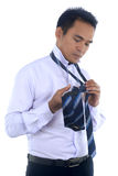 Photo image of a handsome attractive young Asian businessman dressing,making tie. Isolated on white Royalty Free Stock Photo