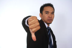 Photo image of a handsome attractive young Asian businessman with thumb down hand. Isolated on white Stock Photos