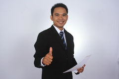 Photo image of a handsome attractive young Asian businessman with thumb up hand. Isolated on white Stock Photos
