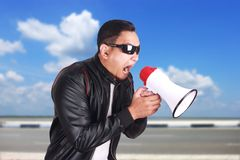 Young Man Shouting with Megaphone, Motivating Concept. Photo image portrait of Asian man shouting with megaphone, mad yelling screaming crazy supporting Royalty Free Stock Photography