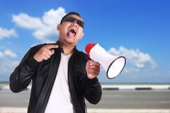 Young Man Shouting with Megaphone, Motivating Concept. Photo image portrait of Asian man shouting with megaphone, mad yelling screaming crazy supporting Royalty Free Stock Photos