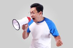 Young Man Shouting with Megaphone, Promotion Concept. Photo image portrait of funny young Asian man shouting with megaphone, mad yelling screaming crazy Royalty Free Stock Images