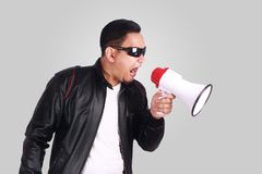 Young Man Shouting with Megaphone, Motivating Concept. Photo image portrait of funny young Asian man shouting with megaphone, mad yelling screaming crazy Stock Photography