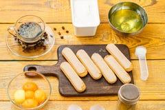 Photo of ingredients for dessert. Savoyardi cookies on cutting board, coffee, cream cheese, yolks, proteins stock image