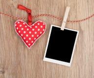 Photo instantanée vide et coeur rouge accrochant sur la corde à linge Images libres de droits