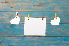 Photo instantanée vide et petit coeur de papier rouge accrochant sur la corde à linge Sur le fond en bois blanc Coeur d'amour acc Images stock