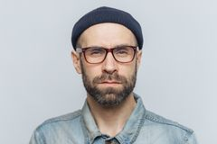 Photo of intelligent confident stylish man with dark thick beard and mustache, looks seriously into camera, poses against grey stu stock image