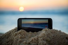Photo of iPhone Capturing a Beach Sunrise. An iPhone propped up by sand is capturing a sunrise in time-lapse mode. Photo taken on a beach in Mexico Stock Images