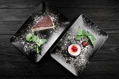 Photo of italian panna cotta dessert with strawberry sirup and cake with nuts and chocolate on the black plate on dark. Wooden background Royalty Free Stock Photography
