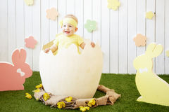 Little girl in yellow dress at the eggshell and rabbits around royalty free stock image