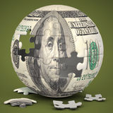 Dollar Globe. Photo of a jigsaw sphere image mapped with a 100 dollar bill on a green backdrop Stock Photography