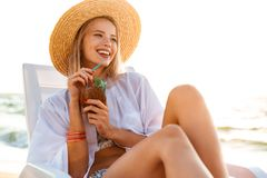 Photo of joyful blonde woman 20s in straw hat drinking exotic co. Cktail while sitting in chaise lounge on beach during summer morning Royalty Free Stock Photos