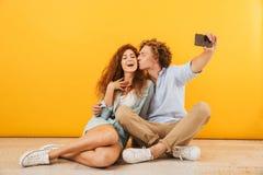 Photo of joyful couple handsome man kissing lovely woman on cheek while sitting on floor together and taking selfie on smartphone. Photo of joyful couple stock photo
