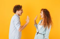 Photo of joyful couple man and woman standing face to face and g. Iving high five isolated over yellow background royalty free stock photography