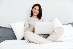 Photo of joyful woman 30s using laptop, while sitting in bed with white linen in cozy apartment. Photo of joyful woman 30s using laptop while sitting in bed with stock photo