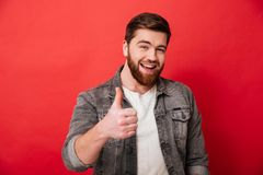 Photo of joyous bearded guy 30s in jeans jacket smiling and show. Ing thumb up on camera isolated over red background stock photos