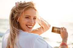 Photo of joyous blonde woman 20s smiling, and taking photo of sunrise above sea, while walking on summer beach. Photo of joyous blonde woman 20s smiling, and stock image
