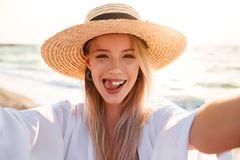 Photo of joyous blonde woman 20s in summer straw hat smiling, an. Photo of joyous blonde woman 20s in summer straw hat smiling and taking selfie while walking at Stock Photo