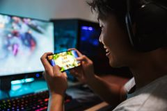 Photo of joyous gamer boy playing video games on mobile phone an. D computer in dark room wearing headphones and using backlit colorful keyboard royalty free stock photos