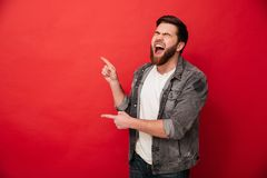 Photo of joyous man in casual clothing bursting in laughter and. Gesturing fingers on copyspace over red background stock images